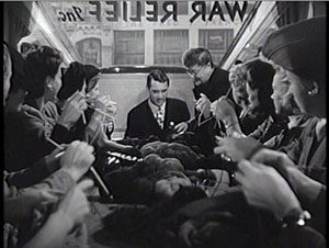 Cary Grant gets a knitting lesson at the War Relief office
